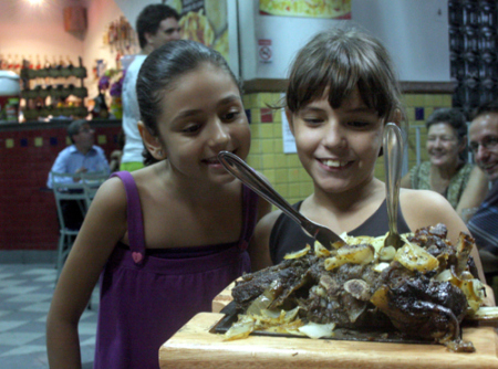 Meninas ficam espantadas, e encantadas, com o costelão recém-saído do forno de bafo, onde fica por horas assando lentamente